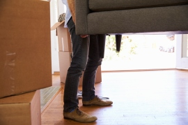 Close Up Of Man Carrying Sofa Into New Home On Moving